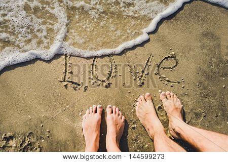 word Love on the sand coast and legs loving couple
