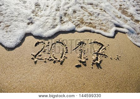2017 message written in the sand at the beach background. Surf the waves on the sand
