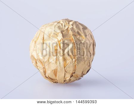 Chocolate Ball In A Gold Foil Paper On A Background.