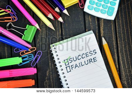 Success text on notepad and office tools on wooden table