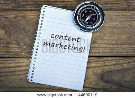 Content marketing text and metallic compass on wooden table