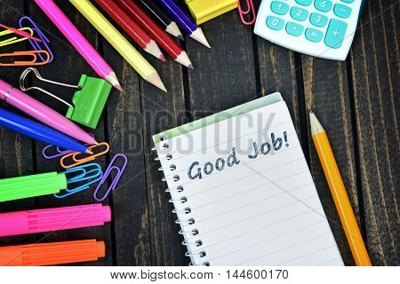 Good Job text on notepad and office tools on wooden table