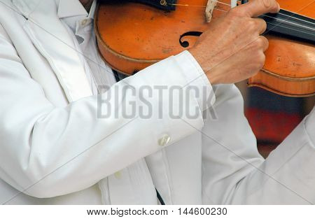 Male classical violinist performing in concert outdoors.