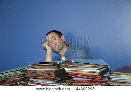 Man bored at work resting his head on his fist with piles of files in front of him.