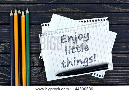 Enjoy little things text on notepad and office tools on wooden table