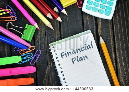 Financial Plan text on notepad and office tools on wooden table