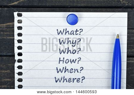 Questions text on page and pen on wooden table
