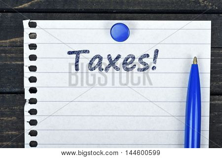 Taxes text on page and pen on wooden table