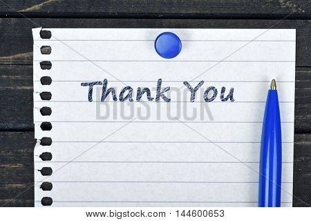 Thank You text on page and pen on wooden table