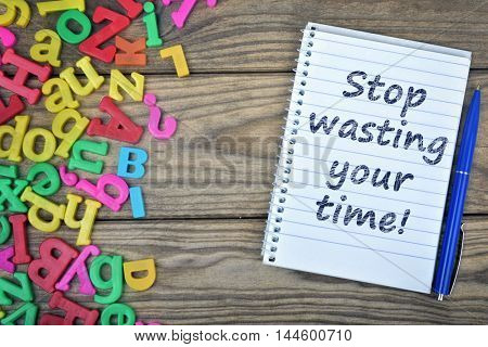 Stop wasting time text on notepad and magnetic letters on wooden table