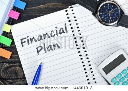 Financial Plan text on notepad and watch on desk