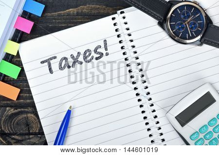 Taxes text on notepad and watch on desk