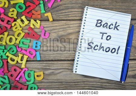 Back to School text on notepad and magnetic letters on wooden table