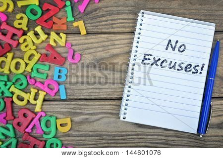 No Excuses text on notepad and magnetic letters on wooden table