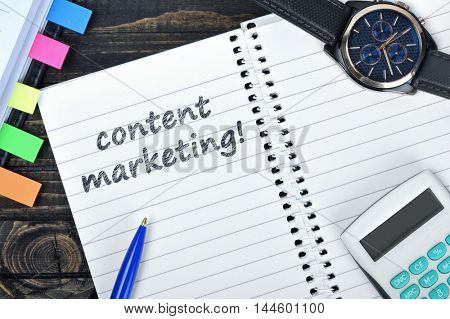 Marketing text on notepad and watch on desk