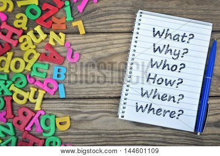 Questions text on notepad and magnetic letters on wooden table
