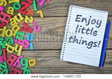 Enjoy little things text on notepad and magnetic letters on wooden table