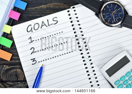 Goals list on notepad and watch on desk
