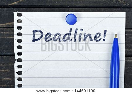 Deadline text on page and pen on wooden table