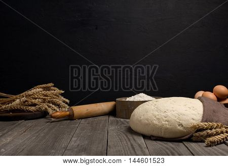 Dough on wooden table with ingredients for the making dough on dark background with space for an object in a bakery