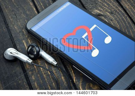 Love music on phone screen and earphones on wooden table