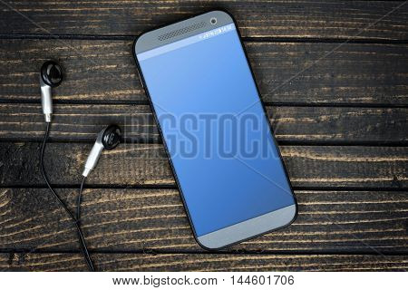 Empty blue phone screen and earphones on wooden table