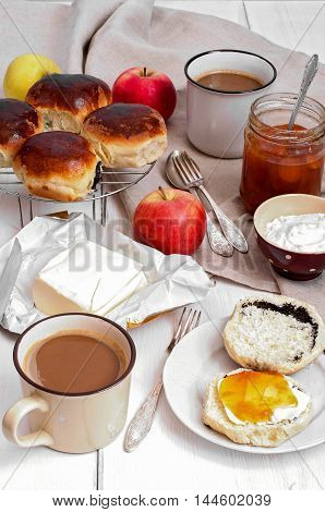 Breakfast: sweet buns with poppy seeds, apricot jam, coffee and butter