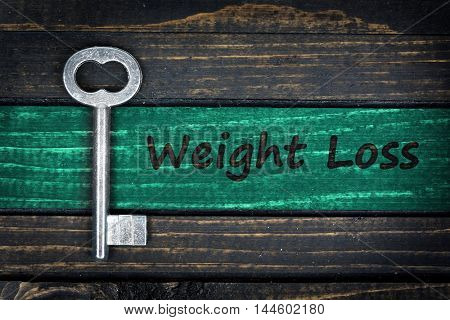 Weight Loss word and old key on wooden table