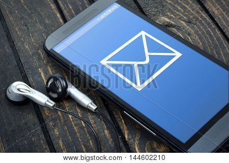 New Email on phone screen and earphones on wooden table