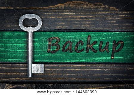 Backup word and old key on wooden table