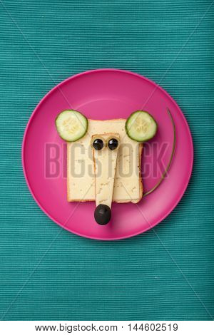 Funny mouse made of bread and cheese on plate and green fabric background