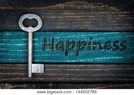 Happiness word and old key on wooden table
