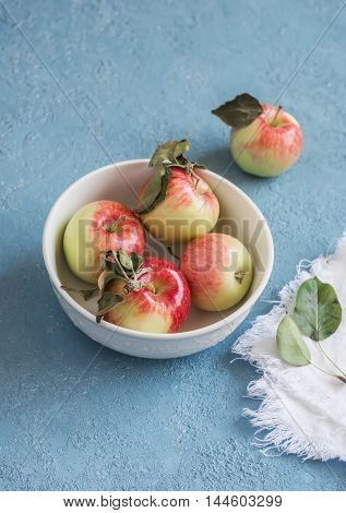 Fresh apples in a bowl on a blue background. Rustic style