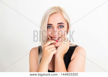 Pretty blonde flirting at camera, close-up. Lovely woman in black dress playfully looking at camera. Flirt, coquette, seduction