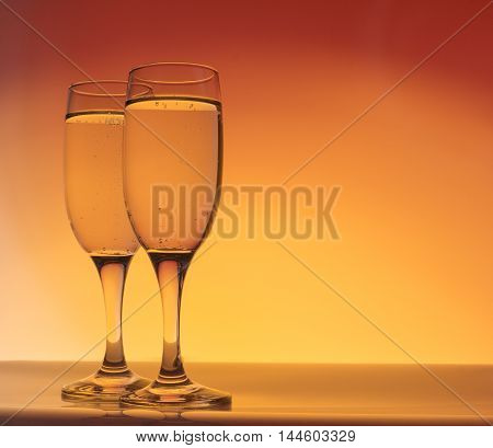 Two champagne glass with bubbles on red and orange background with copy space