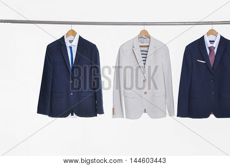 Set of suits Shirts with ties on wooden hangers