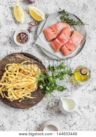 Ingredients for cooking lunch - raw salmon dry pasta tagliatelle cream olive oil spices and herbs. On a light background top view