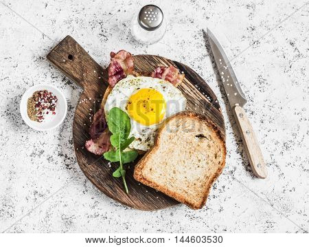 Toast with fried egg bacon and arugula on the wooden cutting board. Delicious breakfast. On a light background top view
