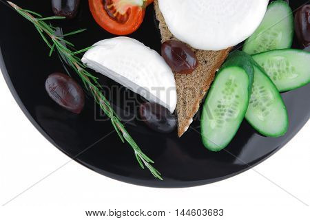 dairy food : soft feta cheese on black plate with bread and vegetables isolated on white