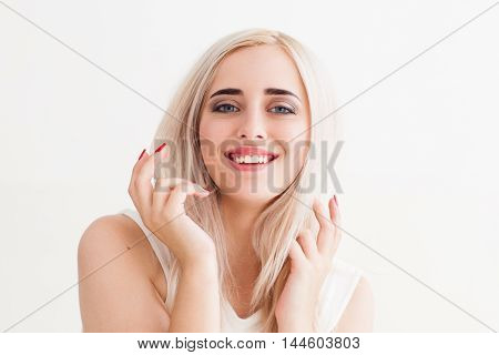 Talk-active blonde gesturing her speech. Portrait of young beautiful laughing woman with raised hands, white background