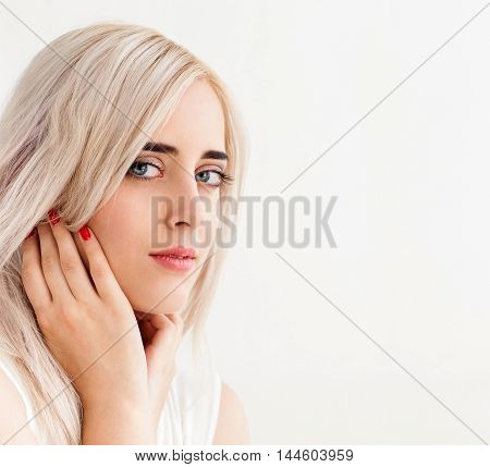Young beautiful scandinavian girl on white background, copy space. Portrait of attractive blonde with perfect skin, close-up, white background