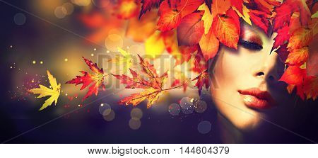 Autumn Woman Fashion Portrait. Fall. Beautiful Model Girl with colourful yellow, red and orange autumn leaves hairstyle. Autumn makeup. Fashion Art design with copy space for your text