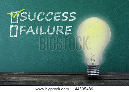 Success text on green board and light bulb on table