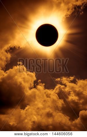 Solar eclipse space with cloud. Abstract fantastic background - full sun solar eclipse glowing on sky and cloudy orange background. Outdoors.