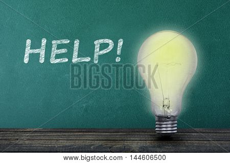 Help text on green board and light bulb on table