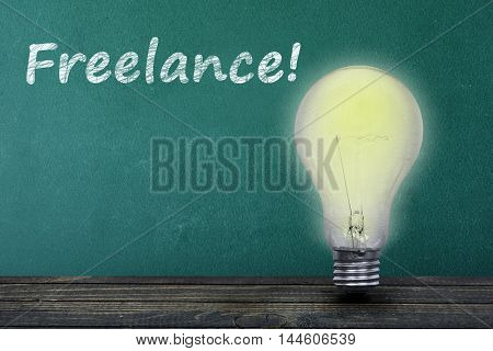 Freelance text on green board and light bulb on table