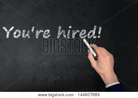 You're hired text write on black board