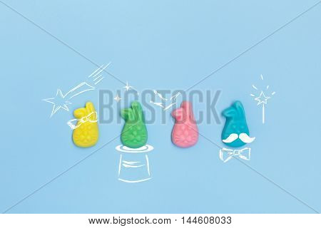 Top view of pastel colored chewy candies in the shape of a rabbit. Painted symbols of magic. Colored yummy candy on a blue background