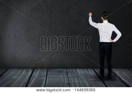 Man about to write on an on empty black board