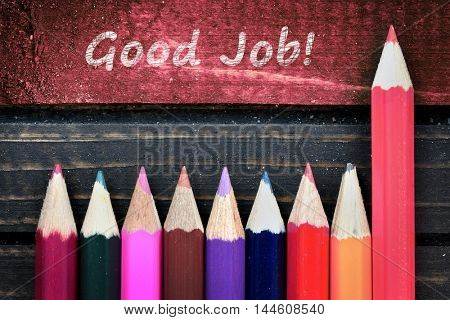 Good Job text and group of pencil on wooden table